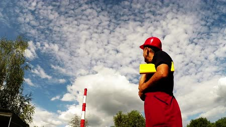 осмотр : Worker with red hard hat using cell phone against a blue sky with white clouds.HD1080p. GoPro HERO3.