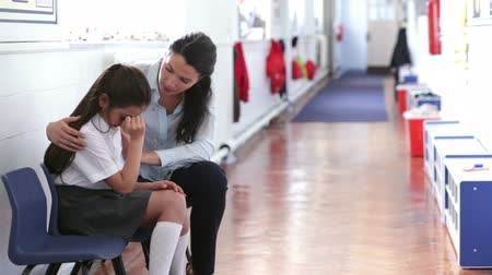 özel öğretmen : A teacher offers support as a young female student looks distressed and upset in the corridor. She has her hands up to her face and the female teacher has her arm around her.