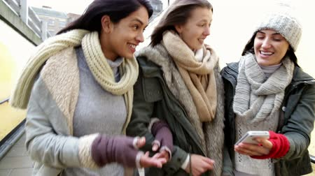construir : Three young women walking together down towards an underpass with their arms linked, looking at something on a smartphone. Stock Footage