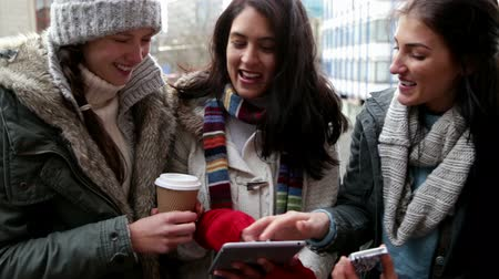 kasaba : Three women looking at a tablet and a smartphone together. They are wrapped up warm and standing on a city balcony. Stok Video