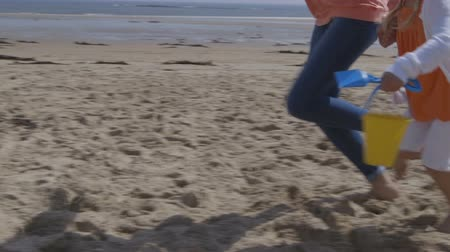 távozás : Shot of a mother and daughters legs only running along the beach. Their faces cannot be seen. The little girl is holding a bucket in her hand as she runs holding her mothers hand in her other.