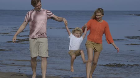 plaz : A happy little boy walks hand in hand with his parents along the beach. They are lifting him up and swinging his as they get closer to the camera. Dostupné videozáznamy