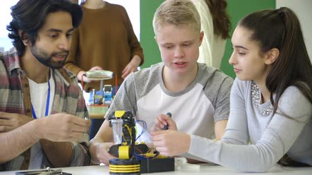 mecânica : Young, male teacher helping his students build a robotic arm. Stock Footage