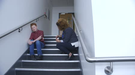 counselling : Young teacher talking to a student who has walked out of his lesson. His teacher is talking to him about how to resolve the situation.