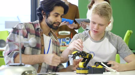 mecânica : Young, male teacher helping his student build a robotic arm.
