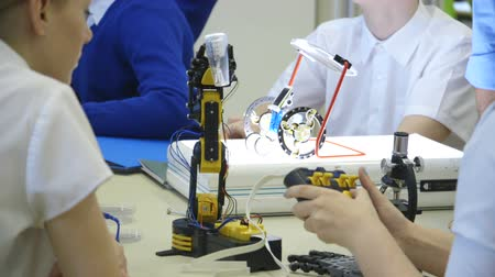 Students using robotic arms in a technology lesson.