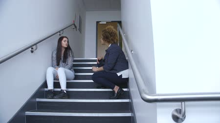 counselling : Young teacher talking to a student who has walked out of her lesson. The teacher is talking to her about how to resolve the situation.