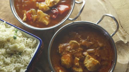kari : Ariel pan view of chicken and vegetable curry with rice. They are each in different dishes on a wooden board.