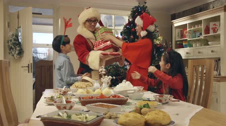 rice cake : Chinese family about to eat a chinese christmas dinner when the father walks in dressed as Father Christmas and bearing presents.