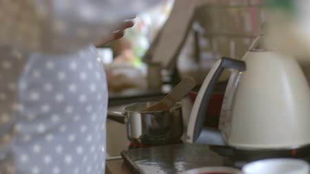 zabkása : Close in video of a womans hands. She is making porridge on the hob of an oven.