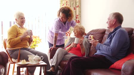 caregiver : Three seniors enjoying tea and cake with their care home worker. Stock Footage