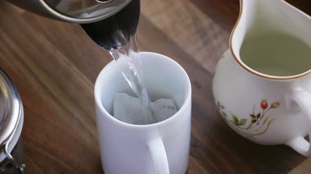 teabag : Close up of a seniors hands making a cup of tea. Stock Footage