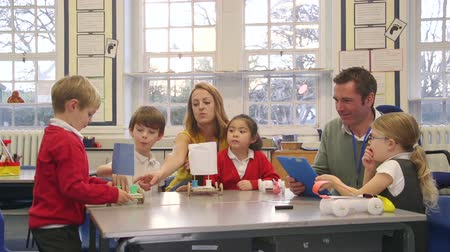 fizik : Primary school students are making their own physics lesson in the classroom using recycled items and crafts equipment. Stok Video