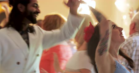 excitação : Hipster couple are dancing together at a wedding with all of the other guests.