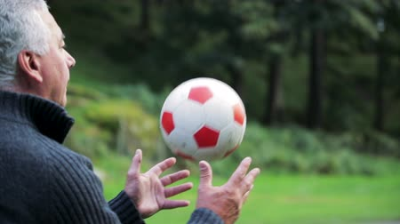 cabeçalho : Senior man is playing football with his grandson in a field.