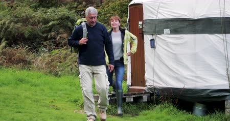 maior : Senior couple are leaving their yurt in the woodlands to go for a hike.