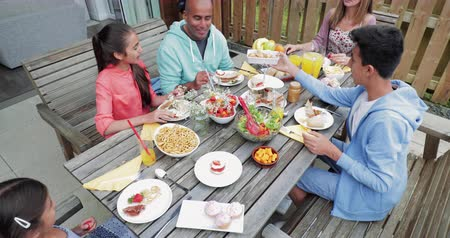 alfândega : Family eating breakfast outside the holiday cottage. Stock Footage