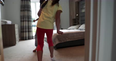 jump away : Two little girls playing, running in the house and jumping onto the bed.