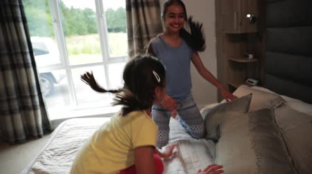 jump away : Slow motion shot of two sisters bouncing on a bed.