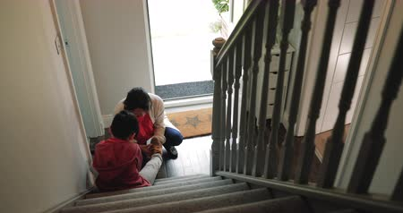 arriving : Little boy arrives home with his grandmother. He sits on the bottom step and his grandmother helps to take his shoes off. Stock Footage