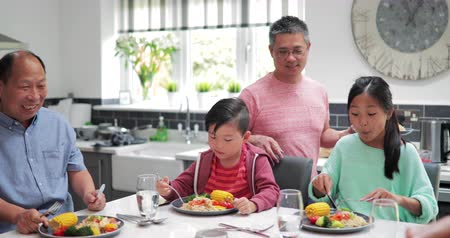 chinese culture : Family are in the kitchen socialising as they enjoy a homemade stir fry dinner.
