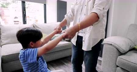 benti : Little boy is spinning round while his father holds his arms. They are in their living room at home.