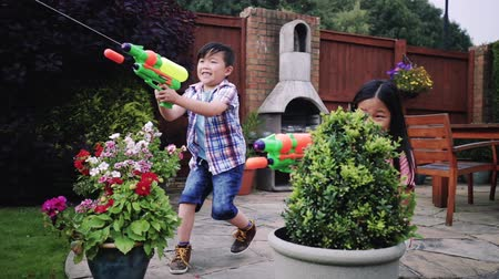 pistol : Siblings are hiding behind plant pots in the garden as they have a water pistol fight in the garden with their family.