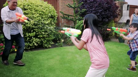 front or back yard : Family of four are having a water fight in the garden with water pistols.