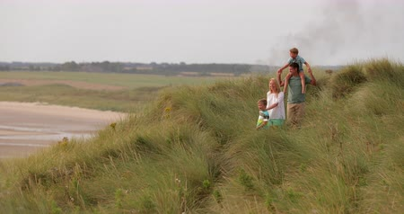 maior : Wide angle, slow motion, of a family walking through the sand dunes while on holiday in Northumberland.