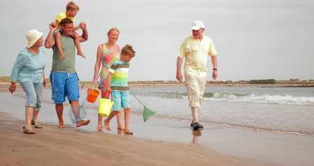 waters : Slow motion shot of a family walking along the waters edge while on holiday in Northumberland. Stock Footage