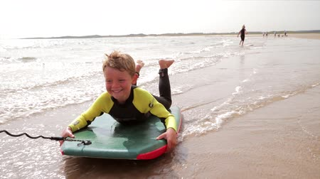 waters : Little boy having fun at the beach, being pulled along on a body board.