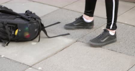 getting ready : Confident freerunner drops his backpack and jacket to the ground before walking to a wall to start a freerunning session. Stock Footage