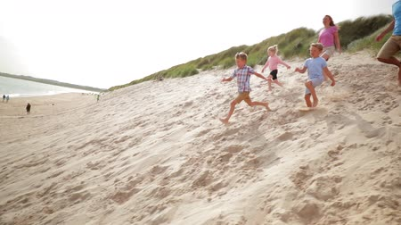 tripping : Slow motion shot of a family racing down a sand dune while on holiday. Stock Footage