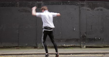legs only : Freerunner is doing a cartwheel corkscrew in a street in the city. Stock Footage
