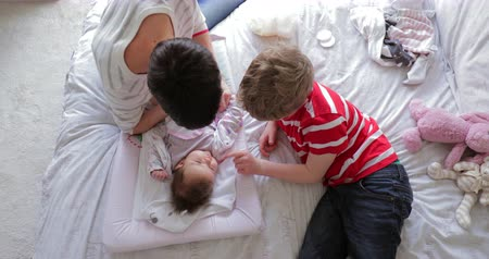 pelenka : Little boy and his mother are being playful with the baby after changing her nappy on the bed.