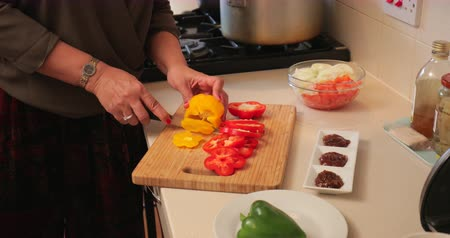 paquistão : Close up shot of a woman slicing peppers to add to the meal she is cooking.