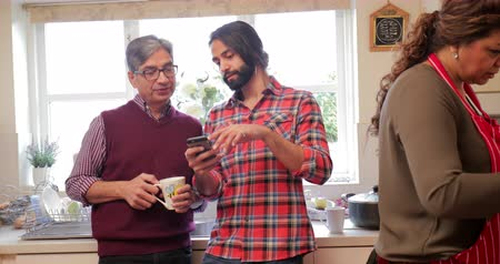 south asian food : Mid adult man is showing his father something on his smart phone in the kitchen while his mum cooks dinner.