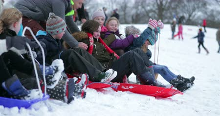 pushed : Children are lined up at the top of a hill on sleds in the snow. They are being pushed down the hill by their parents.