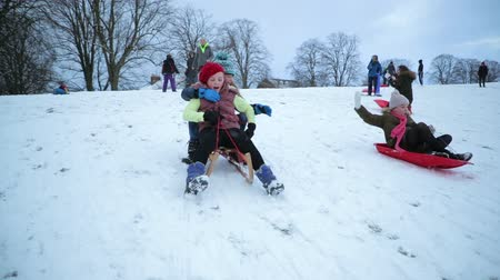 pushed : Little girls are being pushed down a hill on sleds in the snow. Stock Footage