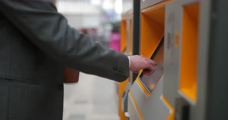 ticket machine : Side view of an unrecognisable person using a ticket machine to buy a ticket for the train.