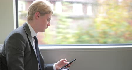 connectivity : Side view of a young adult businessman using his smart phone on the train commute to check social media. Stock Footage