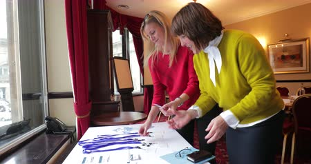 köszönt : Surface level view of a businesswoman finding a name badge lanyard and giving it to a businesswoman. Stock mozgókép