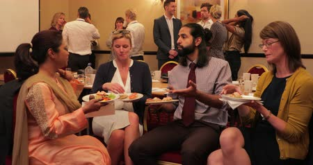 atender : Wide angle view of business people talking and getting to know each other while having a lunch break from the conference. Stock Footage