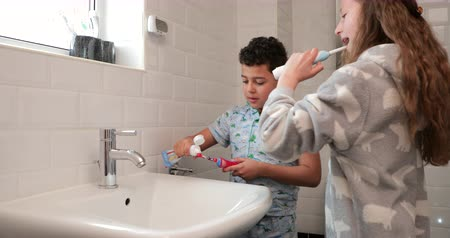 creme dental : Siblings are brushing their teeth together in the bathroom at home. Stock Footage