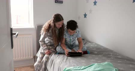 distraído : Little boy is sitting on his bed using a digital tablet when his sister comes in and sits with him.