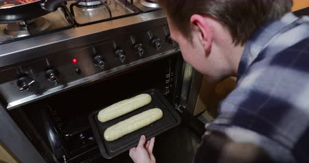 стартер : One young man is putting two garlic bread baguettes in to the oven to cook.