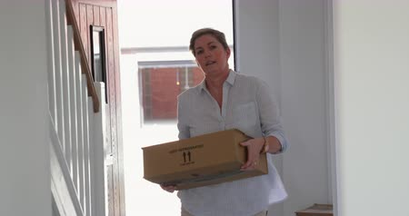 belongings : Mature woman is moving boxes in her new home. Stock Footage