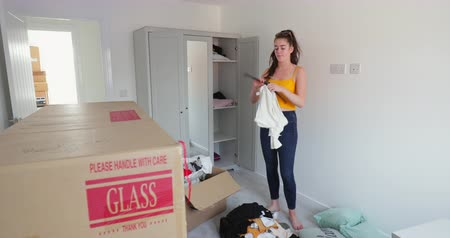 milestone : Teenage girl is hanging clothes up in the wardrobe after moving in to a new home.