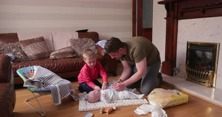 sakk : Little boy helping his dad with fastening up his little brother after his nappy change. Theyre in the living room changing the little boys nappy on his baby mat.