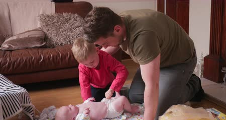 modern manhood : Little boy helping his father in the living room with changing his baby brothers diaper. His dad is helping him fasten the diaper. Stock Footage
